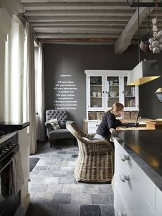 dary gray walls - white kitchen cabinets - heavily white washed ceiling - exposed copper pipes - blue terracotta clay antique floors - dark countertops - modern refined by rustic elements