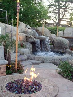 This gorgeous Tropical-style swimming pool includes a spa that cascades into the swimming pool. The fire pit is a great addition to the nearby outdoor bar. It is filled with colored glass and surrounded by a bench and a bocce ball court.