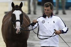 USA's Boyd Martin runs with his horse Otis Barbotiere during horse inspection for the equestrian eventing competition at Greenwich Park July 27.