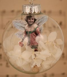 christmas ornament.  Great way to bring the family home for the holidays!  Favourite photos embellished with glitter and add-ons (in this case wings), into the ball with some snow or flower petals.  Adorable for pet photos, too, or even just favourite pieces of art.  All kinds of fun to be had with this craft.  --Meggie