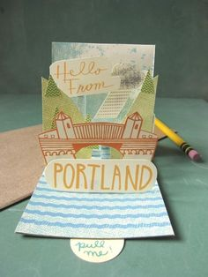 Portland Pop-up Postcard.  Handcrafted pop-up card that's made from silk-screened paper (in 8 different colors). As you pull the tab, the Burnside Bridge, east and west bank, and a rain cloud appear.