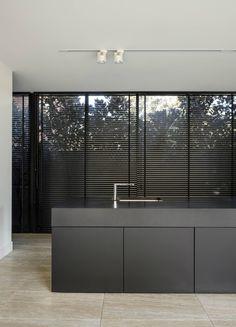 Cozinha com bancada em ilha preta, iluminaçãocom spots em trilhos, piso de mármore travertino. Casa Minimalista em Melbourne por Davidov Partners Architects