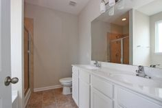 Master bathroom with tiled standing shower, garden tub, dual vanity, and white wooden cabinets.