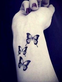 das ist eine der besten ideen zum thema schmetterling tattoo, die ihnen sehr gut gefallen kann   drei kleine, schwarze, fliegende schmetterlinge auf dem handgelenk einer hand einer jungen frau