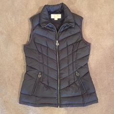 Micheal Kors grey puffer vest Love this! Perfect condition small feet puffer by Michael Kors!  MK zipper pulls. Fully lines, 60% duck down, 40% feather fill. Missing the detachable hood, but who uses those anyway! Michael Kors Jackets & Coats Vests