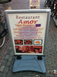 """De poster van restaurant Amor past bij de betekenis van de naam """"Liefde"""". Dit komt door de zachte kleuren en het romantische lettertype."""