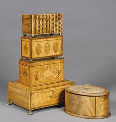 A collection of five George III lidded boxes late 18th/early 19th century comprising a George III satinwood, mahogany crossbanded and marquetry rectangular stationery box with brass paw feet, a George III tea caddy with similar decoration and foliate marquetry throughout, carved to the front JR/1796, a George III parquetry and rosewood tea caddy, a further George III satinwood and harewood tea caddy and a George III oval mahogany and ebony strung casket (5)