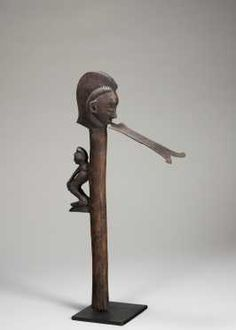 """A fine Pende adze - Pende DR Congo H: 17 """" Carved with the head of the adze in the form of a classical Pende head with male coif, the blade coming from the mouth as the tongue of the head. On the handle, a small crouching figure. Overall excellent patina."""