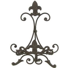 """Possible sign holder? """"Brown Metal Easel with Fleur-De-Lis"""" Measures approximately 8"""" wide x 11"""" tall x 5 1/2"""" deep and will accommodate items up to 1"""" thick. $8.99"""