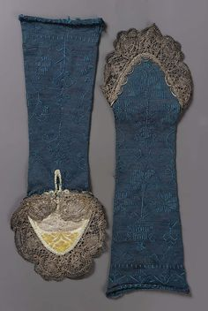 Blue silk knit mitts, embroidered with flowering plants, in blue silk, and trimmed with tarnished silver bobbin lace around hand and lined, over the hand with white, silver, and gold brocaded silk. Blue silk shaded with pink (possibly faded from purple). Collection Achille Jubinal.
