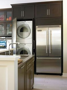 Nearly every wall incorporates storage, yet the space maintains a clean, streamlined appearance. To take advantage of the cabinetry depth needed to surround the refrigerator, the owners included custom walnut doors to conceal a stacked full-size washer and dryer, which had been located in an old porch that was annexed in the remodel.