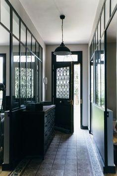La porte d'origine a été restaurée, repeinte et blindée. L'entrée donne accès à la cuisine et au salon. Les verrières en face à face favorisent la luminosité générale.