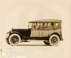 1911 Packard two-toned touring car with light colored folding two-toned, with spare tire carried at back, 7-person touring car