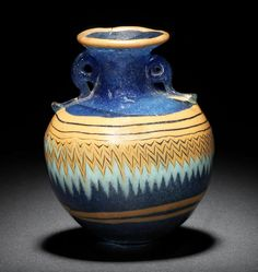 A Greek blue core-formed aryballos  Eastern Mediterranean, circa 6th-5th Century B.C. Possibly from Rhodes, the spherical body with yellow spiral trail above and below finely tooled turquoise and yellow zigzag decoration, with applied yellow trail at the edge of the rim, the bottom with a yellow and turquoise circle, with matching blue applied scrolling handles, 2¼in (6cm) high, mounted