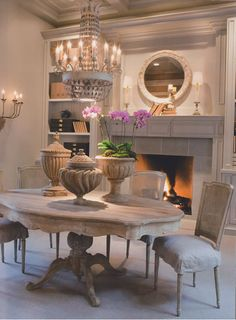 Love the table, chairs, and urns...and the chandelier.