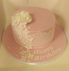 Pink birthday cake with white flowers and lace