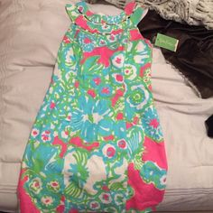Sprig Lilly Pulitzer dress NEVER BEEN WORN. Pink, blue, green , & white funky floral pattern. High neck with cute beaded collard detail at top. Wore the same dress in a different size for Easter last year and it is still one of my favorites! Lilly Pulitzer Dresses Asymmetrical