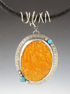 A beautiful orange spiny oyster shell cabochon is set in a sterling silver handmade setting. 2 small turquoise stones and 5 sterling silver