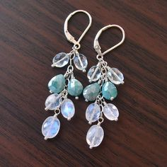 These elegant silverite earrings are the perfect accessory for winter. A group of shimmery, glowing gemstones travels down sterling silver chain in a loose cluster. I have used pale blue aquamarine, blue silverite and rainbow moonstone in this pair, and these three stones complement each