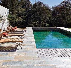El suelo alrededor de la piscina. Alterna baldosas y madera.