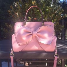 Betsey Johnson Bow All About It Bag Adorable blush/petal pink handbag by Betsey Johnson! It's vegan faux-leather and has a studded trim, double handles, and a removable crossbody strap. Bag is 8 x 10 x 4 inches, strap is 49 inches. There is only a small pen smudge in the inside of the front corner, so you can't see it unless you look for it, but the entire bag is in excellent condition! The spot that looks like it's on the front is from my camera :)) Cheaper on Ⓜ️er! Betsey Johnson Bags…