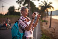 Young woman standing at roadside and photographing by smartphone