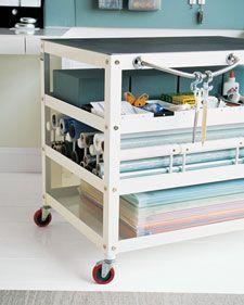 A metal rolling cart serves as a portable, versatile workstation. A cutting board with a grid tops the cart, and frequently used tools hang from a magnetic towel rack. Dedicate it to a household project like gift wrapping.