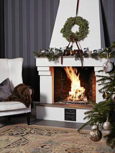 Med fyr i peisen og julepynten på plass, kan godstolen inntas og julen nytes. Peishyllen er dekorert med granbar, levende lys og familiefotografier. Styling: Tone Kroken.