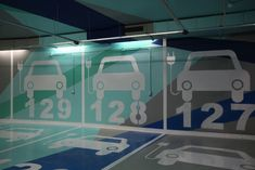 In this garage, built by Teresa Sapey Estudio de Arquitectura, pictograms, various color, and numbers are used in an aesthetically pleasing way to let drivers know they can charge their electric car here.