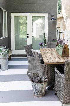This concrete slab patio got an update with painted stripes to make it look like an outdoor rug. Inexpensive way to prolong that ugly concrete slab.