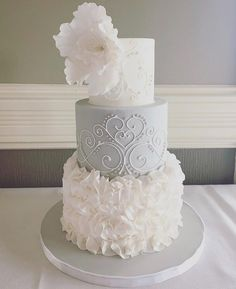 This wedding cake was deisgned to match the brides dress. On the bottom there are layers of gum paste ruffles, while in the middle there is intricate piping, and an open peony made from gum paste on top to finish it off.