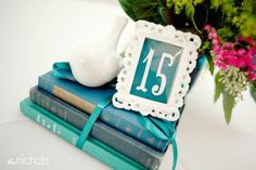 Tales of the great romances described in classic literature depicting 'a love story' like none other is one of my favorite ideas for the theme of a Valentine's Day wedding! Example idea: books, books and more books! I love this idea for numbering tables at 'a love story' themed wedding! Stack romance novels, secured with ribbon and topped with the table number displayed in a beautiful frame. The look is sophisticated and a great way to capture the essence of the theme. Photo Source: The…