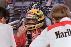 Ayrton Senna talks shop with mechanics from Team McLaren in the pits during time trials in Rio de Janeiro, Brazil 11 March 1988.
