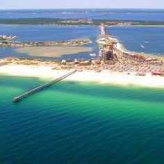 Pensacola Beach with its white sand is a barrier island in the foreground, Gulf Breeze is the peninsula of green in the middle, and Pensacola, Florida, on the mainland is in the background.