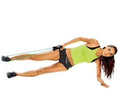 Resistance Band Workout: Work hips, shoulders, biceps, abs, obliques and thighs with the 'Hip Dip.' Start in a left side plank, band wrapped around raised right foot, holding handles in right hand at right hip (as shown). Keeping right leg raised, touch left hip to floor; return to start. Do 12 reps; repeat on opposite side. Do three sets. #SelfMagazine
