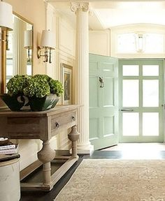 pretty paint color on the door, love the black #2 container with the green hydrangeas. simple and it still evokes a touch of elegance.