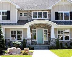 Tan house, white trim, black shutters, bright door