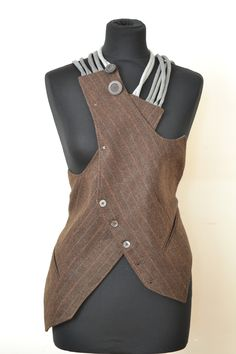 Start with a big vest . Cut it at both shoulders. Criss-cross it in front. Add straps. Alter the back. Embellish. So Burning Man.