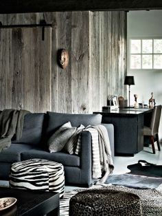 love the wood walls + the grey couch