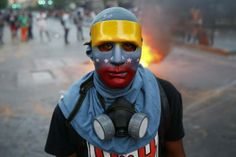 An anti-government protester, wearing a mask in the colors of the Venezuelan flag, stands at a barricade during riots in Caracas April 20, 2014. REUTERS/Jorge Silva