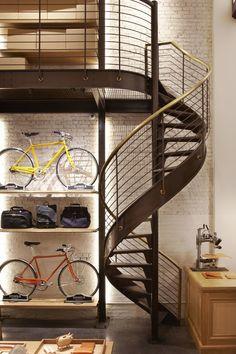 foorni.pl | Sklep Shinola Tribeca – biała ściana z cegieł, metalowe schody, spiralne schody z metalu, rower ozdobą wnętrza, rower jako dekoracja