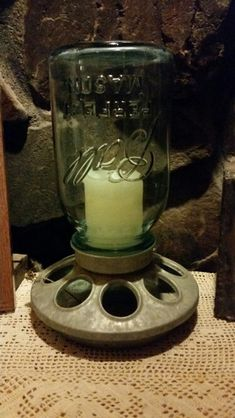 A flameless candle in a old blue mason jar on a chicken feeder makes a cute display for a plain candle.
