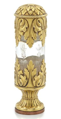 Art Nouveau Gold and Crystal Seal. 18 kt., the circular gold seal centring an engraved crest, topped by a crystal cylinder with an engraved floral design, topped and surmounted by detailed garland and leaf gold work, circa 1900. 3 1/4 x 1 inches.