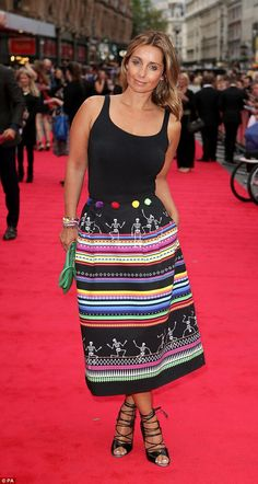 Pop of colour: Louise accessorised her deep tan with a bright green handbag and stacked bracelets