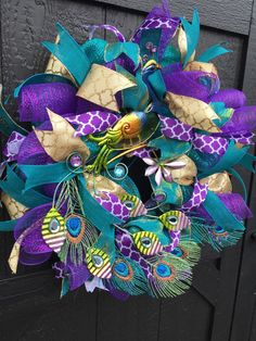 fancywreathladyStunning Peacock Wreath made with teal poly deco mesh and purple deco mesh. The wreath is trimmed with purple, gold, and teal coordinating ribbons and adorned with a beautiful Metal Peacock. Additional peacock feathers are added to give depth and volume to the tail. #peacockwreath, #decomeshwreath #HomeDecor