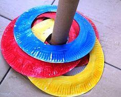 Kartonnen bordjes maken en ze schilderen. Daarna kunnen de kindjes deze rond de kartonnen paal gooien.