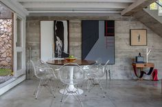 Decoração de casa integrada com a natureza decorada com concreto. Na sala de jantar, mesa redonda branca e de madeira, cadeira transparente, quadros, obra de arte, luz natural. #decoracao #decor #details #casadevalentina