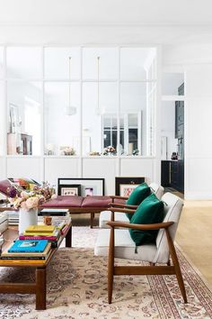 Open glass room divider and white walls in a bright, eclectic living room. | Salon of Morgane Sézalory, photo by Romain Ricard