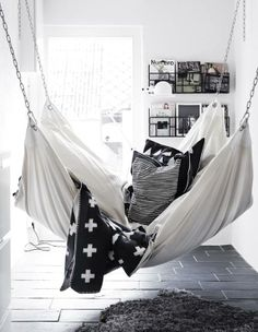 A hammock is the perfect place to recline and relax. Install an indoor hammock for beachy relaxation all year long. For more indoor hammock design ideas, visit domino. Bedroom Sofa, Dream Bedroom, Bedroom Hammock, White Bedroom, Living Room Hammock, Cozy Teen Bedroom, Edgy Bedroom, Monochrome Bedroom, Monochrome Interior