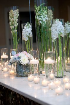 As guests arrived at The Country Club of Birmingham, the foyer table was covered in multiple height glass cylinders containing white stock, white snapdragons, floating candles, as well as votive candles | by Dorothy McDaniel's Flower Market; Mary Margaret Chambliss Photography